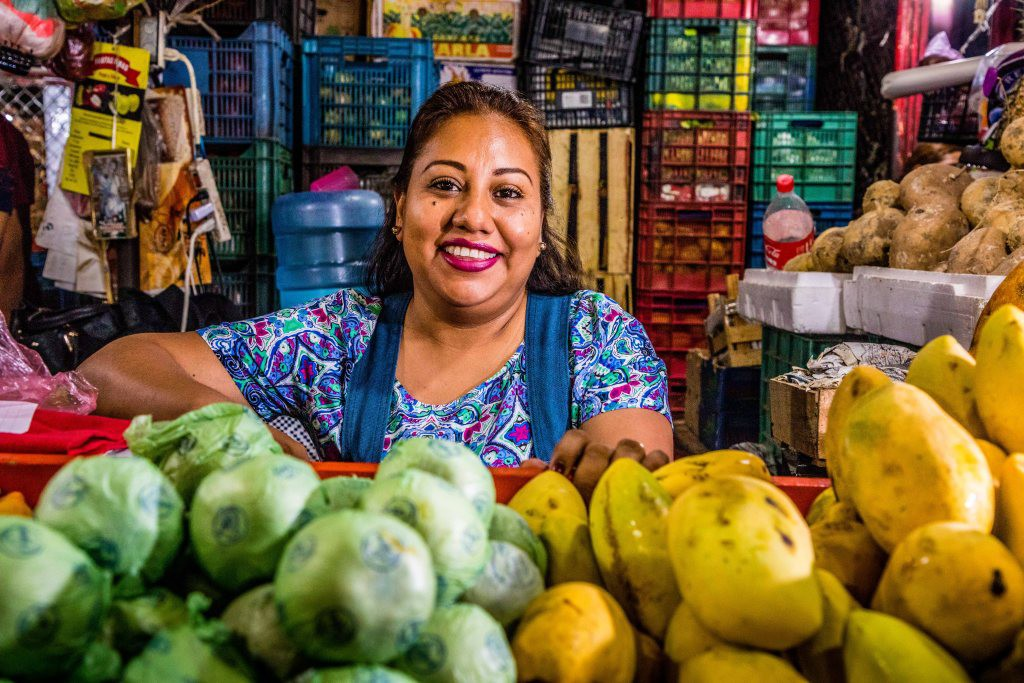 Marta Nelba Barsenas Rangel surrounded by fruit and vegetables at her market stall.